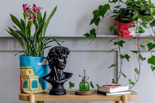 Interior moderno de sala de estar com console de madeira, belas plantas, folha tropical, livro, planta de ar, prateleira, decoração, parede cinza, painéis de madeira e acessórios pessoais em um jardim doméstico elegante.