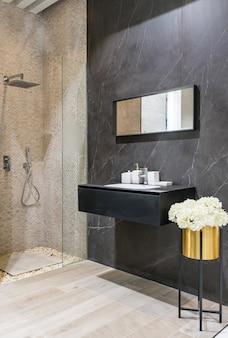 Interior moderno do banheiro com paredes brancas, uma cabine do chuveiro com parede de vidro, um toalete e um dissipador do faucet