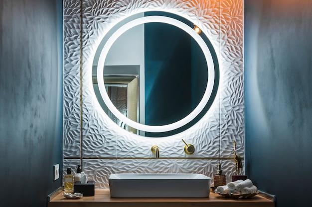 Interior moderno do banheiro com pia branca, torneira dourada e espelho redondo iluminado.