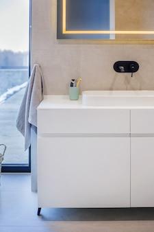 Interior moderno do banheiro com uma pia branca em cima de uma bancada branca e um espelho pendurado acima dela.