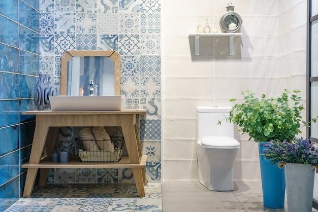Interior moderno do banheiro no primeiro plano da bacia superior contrária usando materiais naturais.