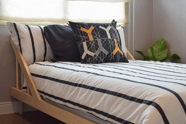 Interior moderno do quarto com travesseiros na base da cama de madeira
