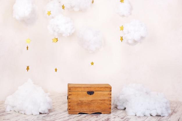 Interior moderno do vintage do quarto de crianças com uma caixa de madeira velha no fundo de uma parede textured com nuvens. interior do parque infantil. peito para brinquedos e jogos para crianças. decoração do quarto dos miúdos