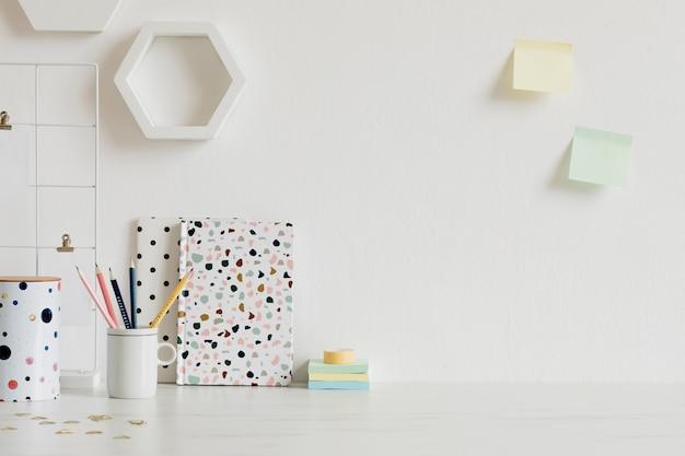 Interior moderno e elegante com acessórios elegantes, suprimentos, notas, bastões de notas, lápis e agenda na decoração escandinava. conceito de escritório em casa. modelo. copie o espaço.