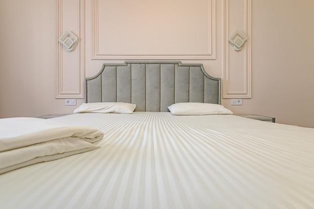 Interior moderno e luxuoso do quarto com cama de casal em tons de bege e marrom