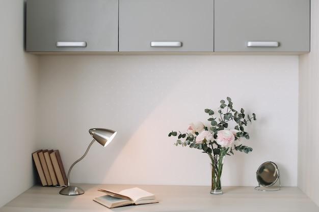 Interior moderno em casa. mesa de madeira com livros e flores. conceito de planejamento e design. ambiente de trabalho. postura plana feminina.