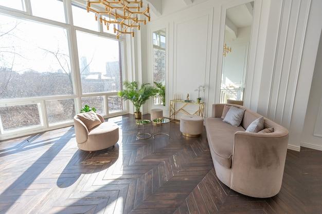 Interior muito luminoso e luminoso de uma sala de estar acolhedora e luxuosa com elegantes móveis bege suave com elementos metálicos dourados, janela enorme para o chão e parquet de madeira