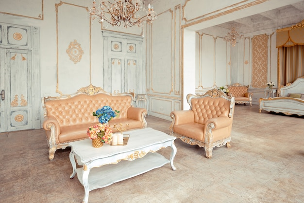 Interior muito rico do apartamento com decorações douradas nas paredes em estilo barroco e móveis luxuosos com pintura dourada.