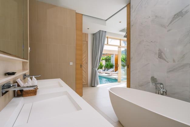 Interior no banheiro com pia, banheira com vista da piscina