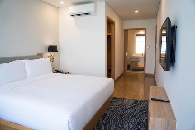 Interior pequeno do quarto de hotel com cama de casal e banheiro.