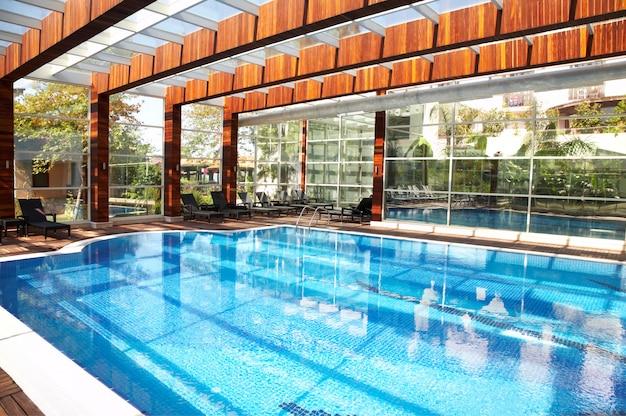 Interior, piscina com teto de vidro.