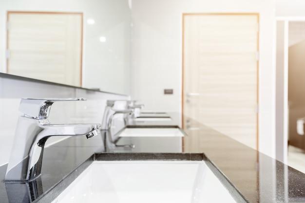 Interior público da casa de banho com torneira da bacia de pia forrado