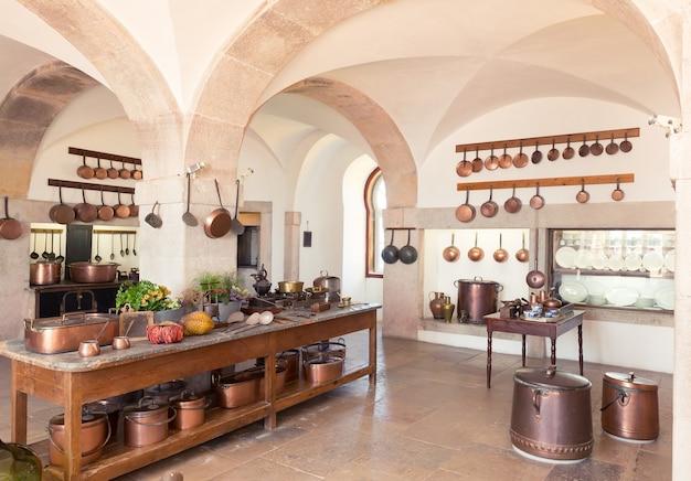 Interior retro da cozinha com potes de latão e armário