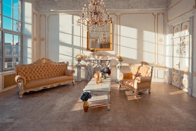 Interior rico do apartamento com decorações barrocas douradas nas paredes e móveis de luxo. a sala está inundada com os raios do sol poente