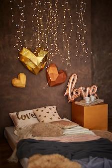 Interior romântico em tons de marrom com cama, travesseiros, cobertores e garland. bandeja de madeira com xícaras. corações 3d na parede. foco seletivo