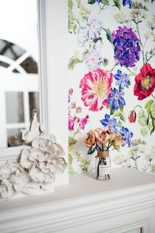 Interior vertical brilhante com papel de parede colorido. um buquê de flores fica em um vaso em uma lareira branca. belo interior de uma sala cara