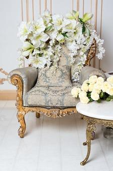 Interior vintage luxuoso no estilo aristocrático com poltrona elegante e flores. retro, clássicos.