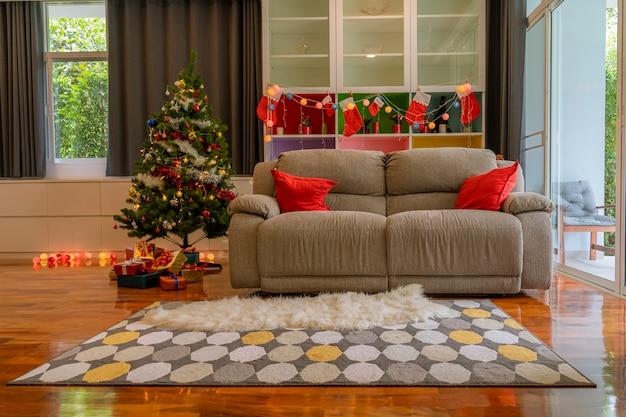 Interiores de quarto com tema de natal, com sofás árvore de natal e caixa de presente