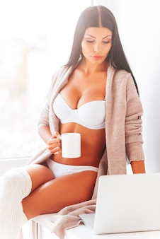 Internet de navegação em casa. mulher jovem e bonita em lingerie e suéter trabalhando em um laptop e bebendo café enquanto está sentado perto da janela em casa