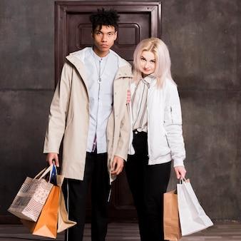 Interracial jovem casal com muitos sacos de compras, olhando para a câmera