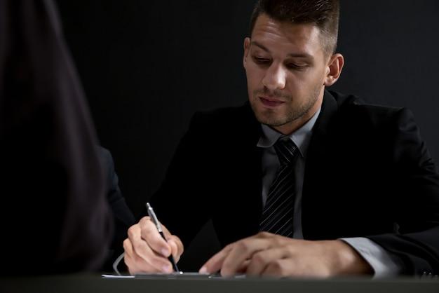 Interrogador tomando nota ao entrevistar suspeito