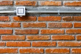 Interruptor tradicional da luz elétrica da casa branca do alternador na posição desligada na parede de tijolo vazia