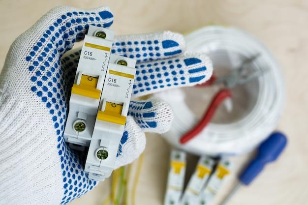 Interruptores automáticos na mão ao lado de fios e ferramentas elétricas