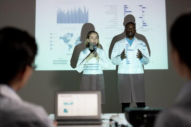 Interseções multiétnicas confiantes em jalecos apresentando projeto científico na frente da comissão na conferência