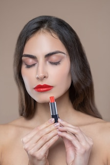 Intuição da mulher. mulher séria e calma com ombros nus, olhos fechados e batom vermelho nos lábios e nas mãos