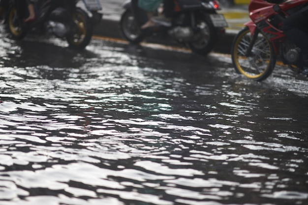 Inundação na estrada pública e motocicletas no engarrafamento