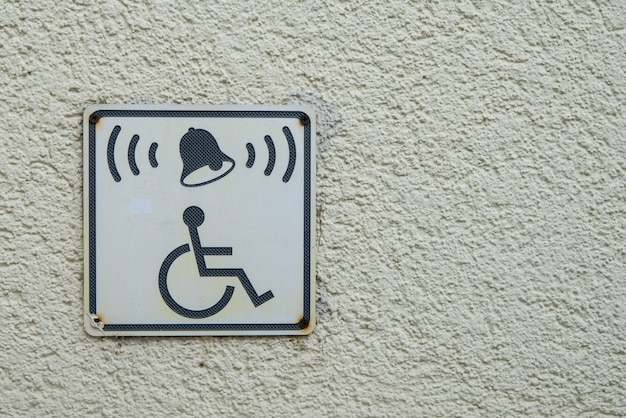 Inválido na cadeira de rodas e sinal de campainha na parede. pessoas com deficiência ajudam com cópia de espaço para texto