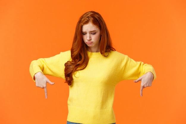 Inveja, mulher ruiva bonita triste e mal-humorada camisola amarela, olhando e apontando para baixo