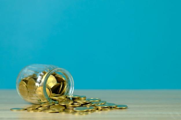 Inventa pilhas e dinheiro da moeda de ouro no frasco de vidro na tabela com fundo verde, para salvar para o conceito futuro da finança da operação bancária.