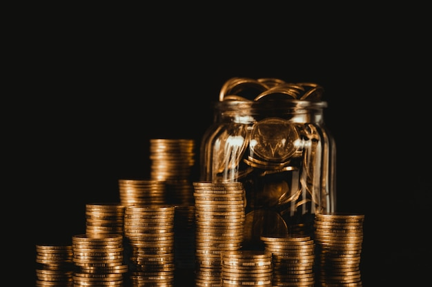 Inventa pilhas e dinheiro da moeda de ouro no frasco de vidro no fundo escuro, para salvar para o conceito futuro da finança da operação bancária.