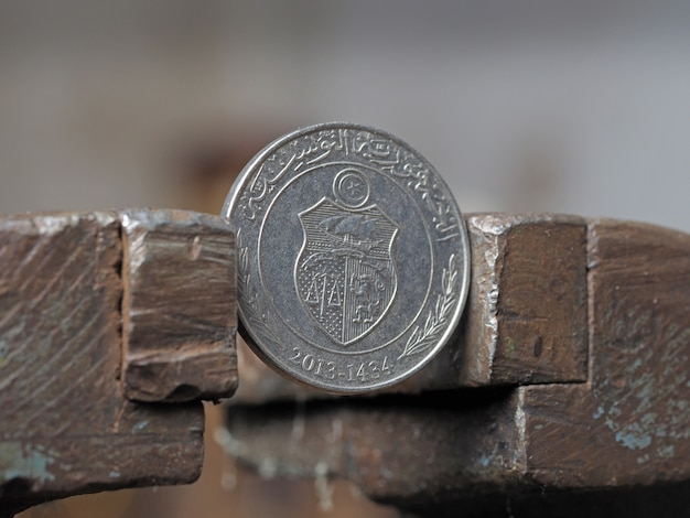 Invente um dinar tunisino, preso em uma morsa de metal