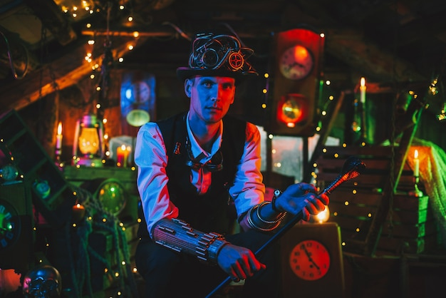 Inventor masculino em um terno steampunk, cartola, óculos com uma bengala na mão em uma oficina de relógio. conceito de cyberpunk pós-apocalipse