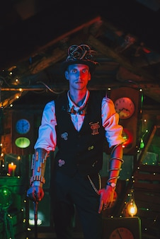 Inventor masculino em um terno steampunk, cartola, óculos e uma bengala na mão em uma oficina de relógios