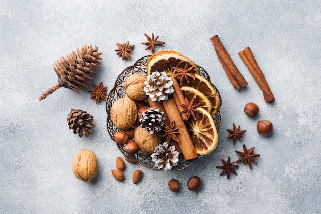 Inverno alimentos ingredientes nozes cones laranjas canela anis estrelado em uma tigela.