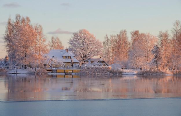 Inverno, amanhecer, casa na margem do lago