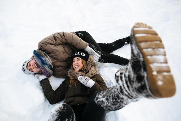 Inverno. casal jovem alegre se divertindo na neve. história de amor de inverno.