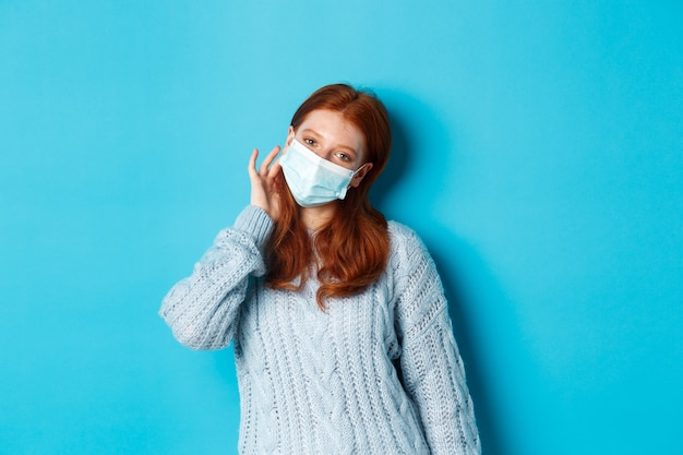 Inverno, covid-19 e conceito de distanciamento social. adolescente ruiva fofa, usando máscara facial e prendendo uma mecha de cabelo atrás da orelha, olhando para a câmera, em pé sobre um fundo azul
