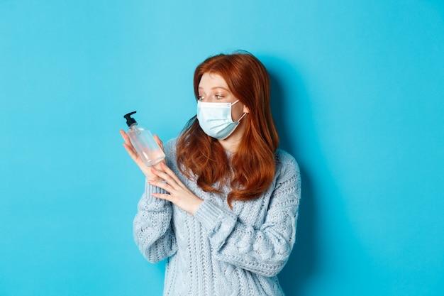 Inverno, covid-19 e conceito de distanciamento social. jovem ruiva com máscara facial mostrando desinfetante para as mãos, demonstrando anti-séptico para desinfecção, em pé sobre fundo azul