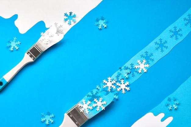 Inverno em azul e branco com pincéis carregados com flocos de neve de papel