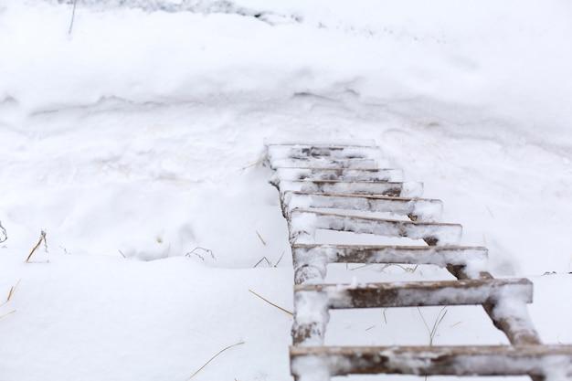 Inverno, escadas de madeira na rua, cobertas de neve.