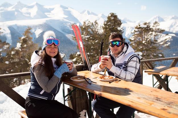Inverno, esqui - esquiadores almoçando nas montanhas de inverno.