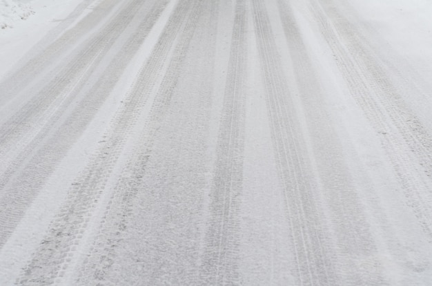 Inverno - estrada coberta de neve com vestígios de pneus e pegadas