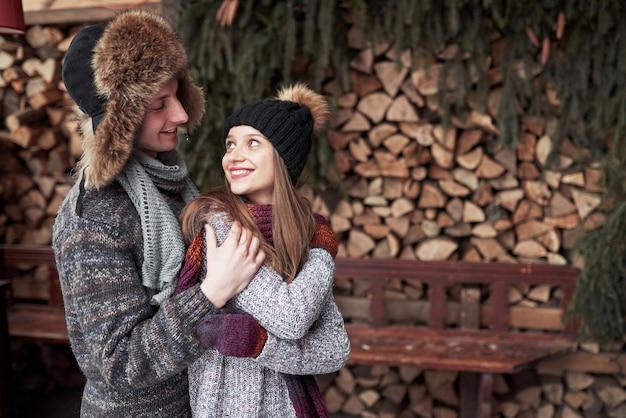 Inverno, férias, casal, natal e pessoas - sorrindo homem e mulher de chapéu e cachecol abraçando sobre neve e casa de campo de madeira