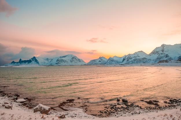 Inverno. fiorde norueguês rodeado por montanhas cobertas de neve no início da manhã. céu rosa do sol nascente refletido na água