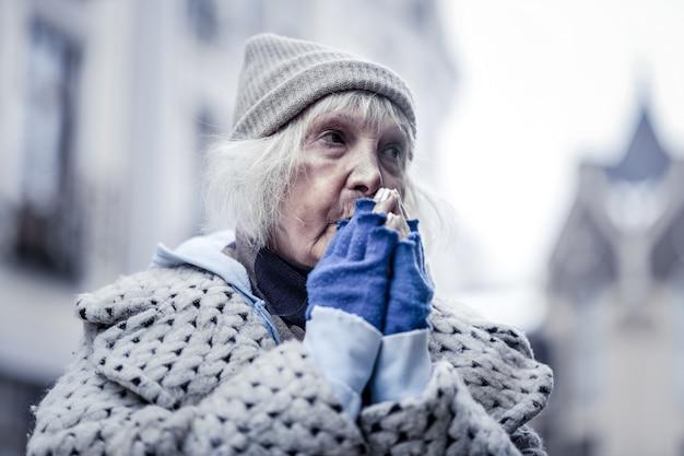 Inverno frio. mulher pobre e infeliz sentindo muito frio enquanto fica do lado de fora no inverno
