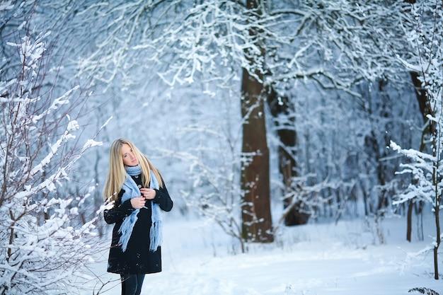 Inverno. jovem caminhando pela floresta nevada e sorrindo